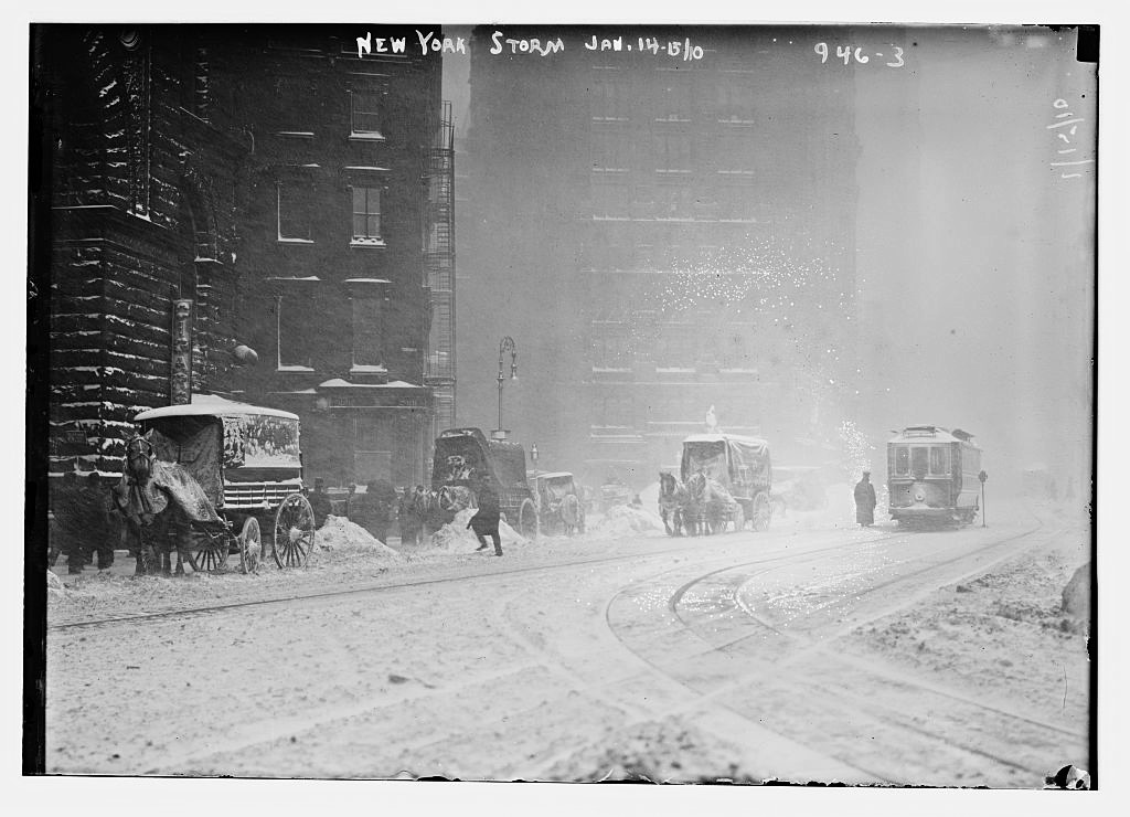 Horse-drawn wagons on snowy street, NY snow storm 1910